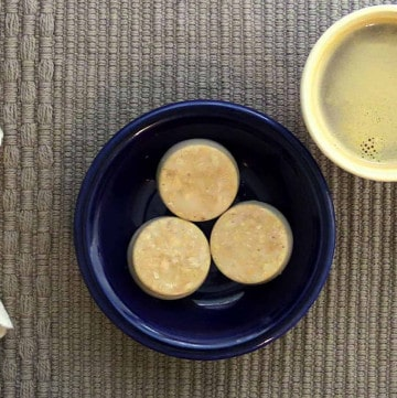 three almond crunch fat bombs shown in a blue bowl with a cup of coffee beside it