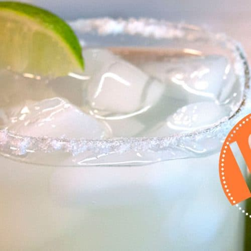 low carb margarita shown in an icy, salted glass with a lime beside it and tequila bottle in the background