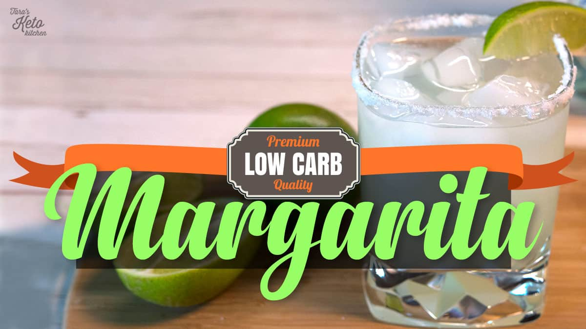 low carb margarita shown in an icy, salted glass with a lime beside it on a cutting board