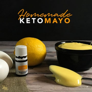 Homemade Keto Mayo on a bowl on the table with lemon essential oil and lemons