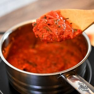 low carb pizza sauce shown on a wooden spoon over a metal pan