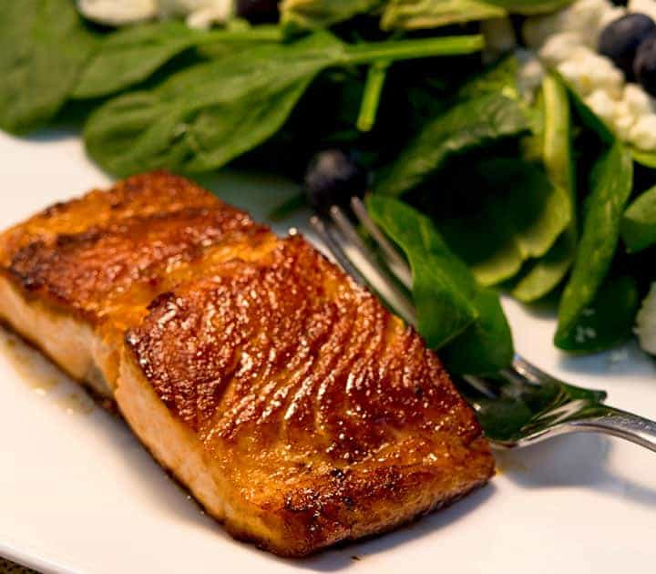 keto maple glazed salmon on a plate next to spinach salad