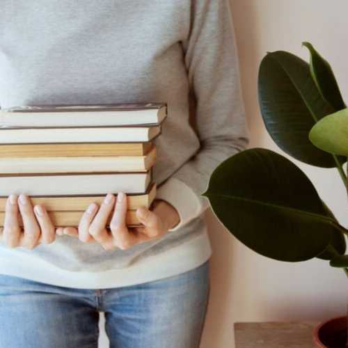 a woman holding a stack of books for the keto diet