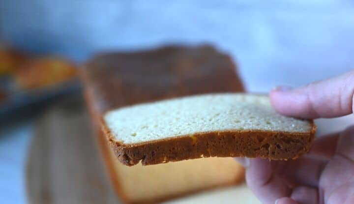 hand holding low carb keto bread showing how sturdy it is