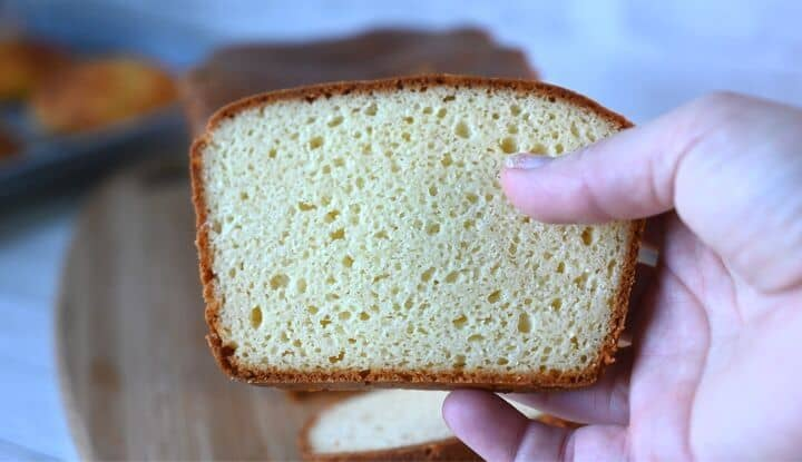 hand holding a slice of keto bread with a close up of the texture of this low carb bread recipe