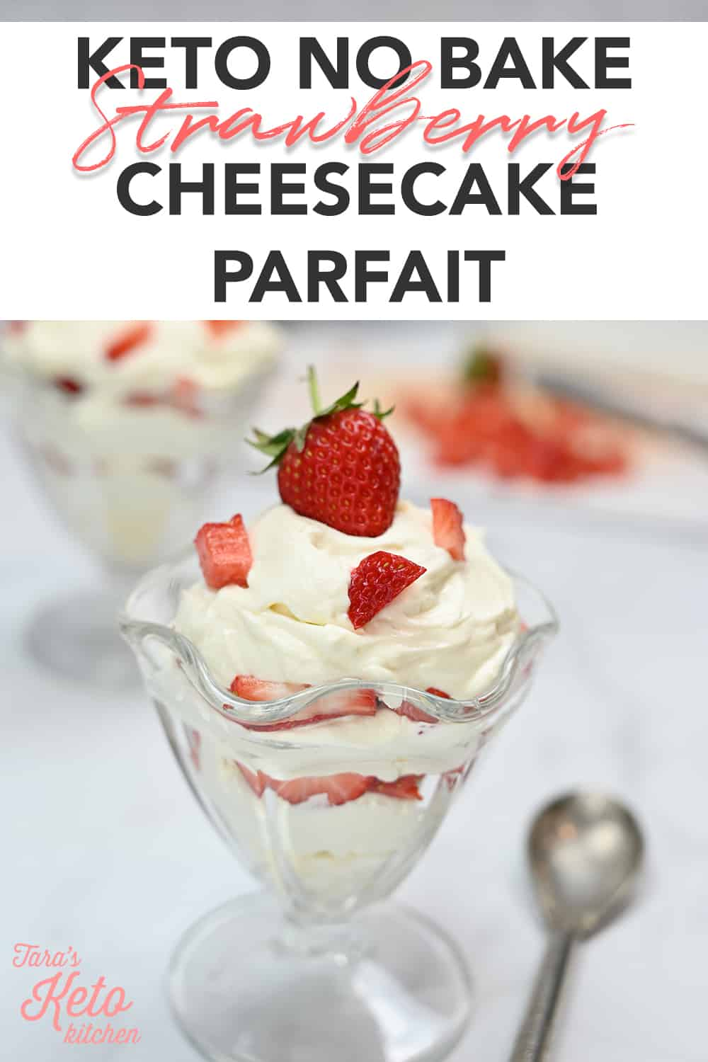 Keto No Bake Strawberry Cheesecake Parfait built in layers in a tall, glass parfait dish with an almond flour crust with a spoon sitting beside it