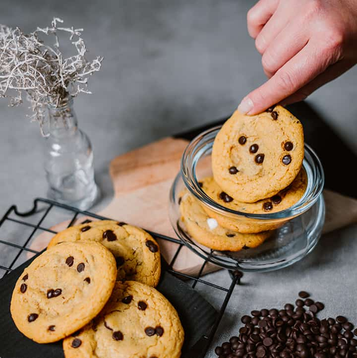 top view of a hand pulling out a Keto Chewy Chocolate Chip Cookie from a jar