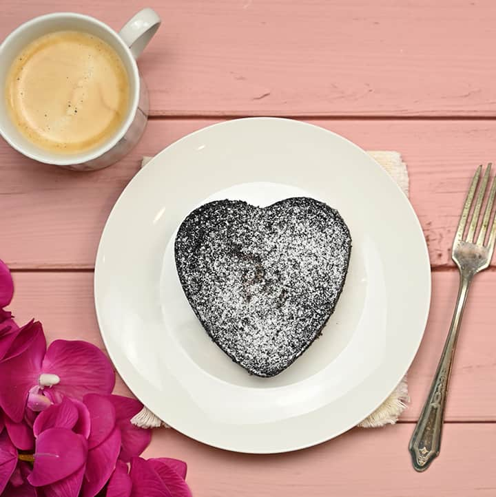 top view of a mini keto heart cake with powdered sugar substitute and coffee on the side