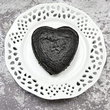 Mini Keto Heart Cake on a plate sprinkled with powedered sugar