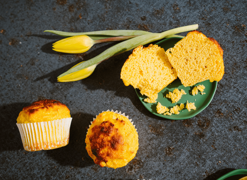 top view of 2 Keto Corn Bread Muffins with a 3rd muffin cut open, 2 yellow flowers lay by the plate