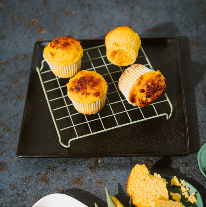 four keto cornbread muffins on a cooling rack