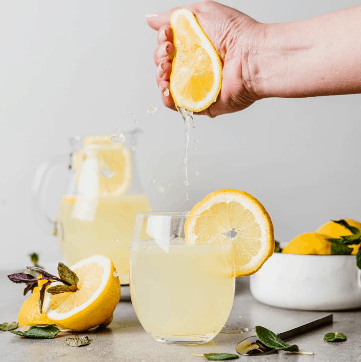 squeezing lemon juice into a glass of Homemade Keto Lemonade